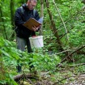 Homme en pleine nature, effectuant un recensement de tritons. Il a des bottes, un seau et un carnet dans lequel il note ses observations. Il est au bord d'une mare. Etude de la variation de population d'amphibiens. Protection des espËces, suivi des populations, dans le cadre d'un contrat Natura 2000.