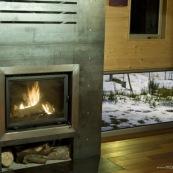 Poele à bois dans un chalet de montagne. Contraste entre le feu et la neige à l'extérieur. Chalet en bois, moderne. En soirée. Chauffage. Insert. Dans les cévennes, mont aigoual.