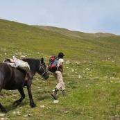 Berger et son cheval ramenant des provisions à sa cabane en montagne, gravissant du dénivelé. Le cheval porte les provisions. Le berger le précede. Vue de trois quart arrière.