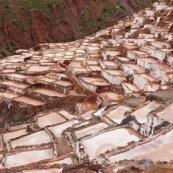 Terrasses des salineras de Maras. Une personne remplie des sacs de sel. Exploitation de sel. L'eau d'une source riche en sel est guidée dans les terrasses, l'eau s'évapore, reste le sel. Balcons. Pérou.