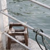 Petit banc en bois décérépi au bord de l'eau avec barrière. Hong-kong.
