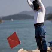 Pilote de cerf-volant traditionnel ‡ Hong-Kong, en Chine. Entrainement au cerf-volant de combat monofil mais directif. VisiËre pour se protÈger du Soleil, et Èquipement complet pour piloter le cerf-volant, au bord de la mer. Pilote debout, en train de prÈparer son cerf-volat, rouge. DÈvidoir en main il s'apprete ‡ le mettre en vol. Il est ÈquipÈ pour piloter son cerf-volant.