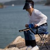 Pilote de cerf-volant traditionnel ‡ Hong-Kong, en Chine. Entrainement au cerf-volant de combat monofil mais directif. VisiËre pour se protÈger du Soleil, et Èquipement complet pour piloter le cerf-volant, au bord de la mer. Pilote assis sur une chaise, avec le dÈvidoir en main, roulant sur des supports attachÈs aux cuisses, et permettant de rembobiner ou dÈbobiner avec rapiditÈ le fil.