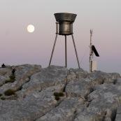 Station meteorologique en montagne avec la lune en arriere plan, paysage lunaire. Pluviometre.