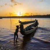Coucher de soleil en Guyane. Sur le fleuve Maroni. Pirogue et enfants avec leur pere sur la pirogue. Village de Saint Jean du Maroni.