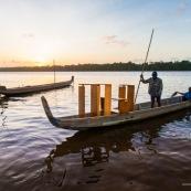 Coucher de soleil en Guyane. Sur le fleuve Maroni. Pirogue transportant du mobilier contemporain DISSI en bois massif de Guyane.