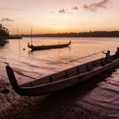 Coucher de soleil en Guyane. Sur le fleuve Maroni. Pirogue et enfant sur la pirogue.
