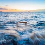 Mobilier en bois massif de Guyane console DISSI dans la mer avec au fond les ilets le père et la mère. Levé du soleil.
