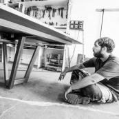 Atelier d'un artisan menuisier en train de réaliser une grande table de réunion en bois massif de Guyane.