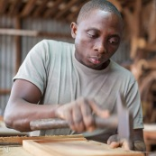 Artisan menuisier en train de réaliser du mobilier en bois massif de Guyane pour la marque DISSI.