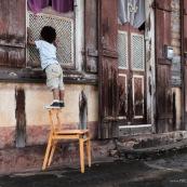 Petit garçon enfant en train de monter sur une chaise de marque DISSI (bois massif de Guyane) et regarde par la fenêtre d'une maison créole.