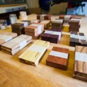 Echantillons de bois de Guyane sur une table.  Amarante, cèdre, balata, saint martin rouge, bagasse, bois seprent, boco, wacapou, manil, gaiac...