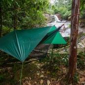 Carbet bache en foret tropicale amazonienne en Guyane. Hamac tendu entre deux arbres et bache tendue au dessus pour passer la nuit. Camping. Chute d'eau en arriere plan.