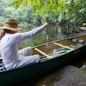 En canoe, peche a l'Aymara. Hoplias aimara. Homme en canoe ayant attrapé un poisson. En Guyane, foret tropicale amazonienne.