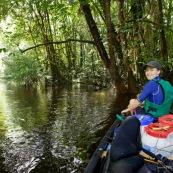 Kayak, kayaliste, en Guyane, foret tropicale amazonienne. Sur une riviere (crique). En bout de canoe.