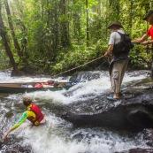 Passage de canoe dans la foret tropicale amazonienne. Expedition en Guyane.  Arret observation en haut d'un saut, chute d'eau. Passage du saut a la corde (cordelle).