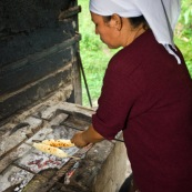 Femme bolivienne en train de préparer de la cuisine traditionnelle (des sonsos : manioc appele egalement yuca, et fromage frais) au feu de bois, dans une petite maisonnette dans la jungle, foret en arriere plan. Bolivie.
