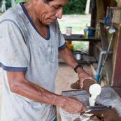 Decoupe du manioc (cramagnoc) dans un carbet en foret. Perou. Dans la cuisine.