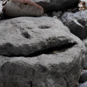 Gros caillou en forme de tête de bonhomme, visage minéral, silouhette humaine dans la roche, homme, yeux, bouche, drole de monstre.