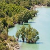Vue sur le lac de Barrea. Italie, abords du parc national des Abruzzes (Parco Nationale díAbruzzo, Lazio e Molise). Lac de montagne. Paysage. Eau turquoise, l'ÈtÈ. Lac artificiel. Arbres ayant les pieds dans l'eau.