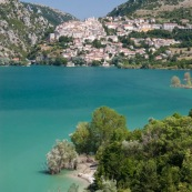 Massifs montagneux des abruzzes, en montagne. Vue sur le lac de Barrea, et au bout du lac la ville (village) de Barrea. Italie, abords du parc national des Abruzzes (Parco Nationale díAbruzzo, Lazio e Molise). Au bord du lac de BarÈa, lac de montagne. Paysage. Eau turquoise, l'ÈtÈ. Lac artificiel. Village traditionnel de montagne. Arbres les pieds dans l'eau.
