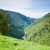Paysage champetre en montagne avec rivière et paturage.