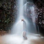 Homme sous une cascade en Guyane (Ouanary). Baignade.