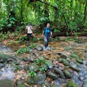 Homm eet femme traversent une rivière en forêt tropicale, bassin amazonien, pérou.