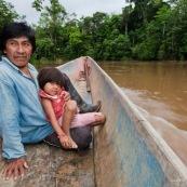Amerindien dans une pirogue. Indigene Waorani (huaorani). Avec sa petite fille et sa sarbacane. Dans la foret tropicale amazonienne.