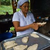 Femme en cuisine en train de cuisiner des empanadas.