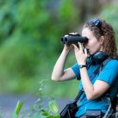 Femme avec des jumelles en train d'observer dans la nature.