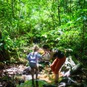Guyane. Femme et jeune fille enfant en train de se baigner dans une rivière (crique) en pleine foret (sentier du Rorota).  Foret tropicale amazonienne.