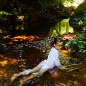 Guyane. Jeune fille enfant en train de se baigner dans une rivière (crique) en pleine foret (sentier du Rorota). Foret tropicale amazonienne.
