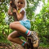 Guyane. Jeune fille enfant en train de grimper sur une liane en foret tropicale amazonienne.