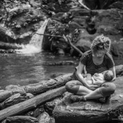 Touristes. Femme et son bebe en train d'allaiter. Allaitement maternel. En foret tropicale amazonienne.  Tourisme. Crique (riviere). Guyane.