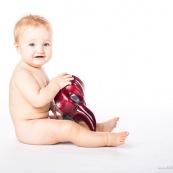Portrait de bebe avec un masque rouge venitien. Italien. Masque de bal de carnaval. En Guyane.