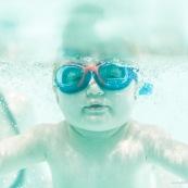 Portrait de bebe sous l'eau. Sa maman a proximite. Bebe avec des lunettes sous l'eau dans une piscine. En train d'apprendre a nager.