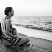 Guyane. Sur la plage des salines (Remire Montjoly) une femme et son bebe en train de regarder le coucher de soleil. Assis sur un tronc de palmier.
