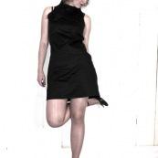 Mode. Femme en robe noire. Portrait. Collants. Adossée contre un mur. Jambes croisees.