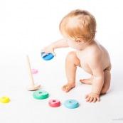 Bebe petite fille en train de jouer avec un jeu en bois. Anneaux a passer sur une tige. jeu d'adresse. Habilete. Jouet. Ronds perces.