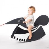Bebe petite fille sur un fourmillier a bascule (sorte de cheval a bascule version fourmillier). En Guyane, jouet en bois. Jeu.