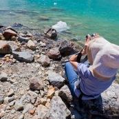 Touriste en train d'obeserver avec des jumelles au bord de l'eau, lac turquoise en Patagonie argentine.