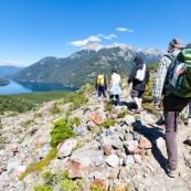 Randonnée en Patagonie : guide et touristes. Sac au dos, en montagne. Vue de derrière. En descente vers un immense lac.