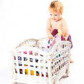 Bebe petite fille . Portrait. En train de s'amuser avec des vetements et un chariot. Habits. Enfant.