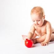 Bebe avec une balle rouge. Portrait.