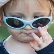 Bebe petite fille enfant. Reflet dans ses lunettes de sa main avec du pain. En train de manger.