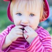 Bebe petite fille enfant en train de manger des cerises. Bouche sale.