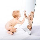Portrait de bebe avec un miroir. Il se regarde dans la glace.