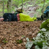 Randonneuse (randonneur) en bivouac ‡ mÍme le sol, en forÍt l'ÈtÈ. Femme allongÈe en train de dormir en forÍt, avec son sac ‡ dos posÈ ‡ cotÈ d'elle, sur un lit de feuille morte. Sieste aprËs l'effort.   Aux abords du Parc National des Abruzzes en Italie.