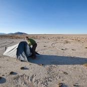 Sur un lac asseche, pres d'Oruro. Camping sauvage, tente. Femme au premier plan.